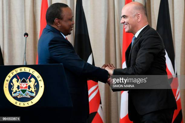 Swiss President Alain Berset shakes hands with his Kenyan counterpart President Uhuru Kenyatta during a joint press conference at the State House in...