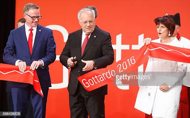 Swiss President Johann SchneiderAmmann cuts the ribbon next to Swiss Federal Railways CEO Andreas Meyer and Swiss Transport Minister Doris Leuthard...