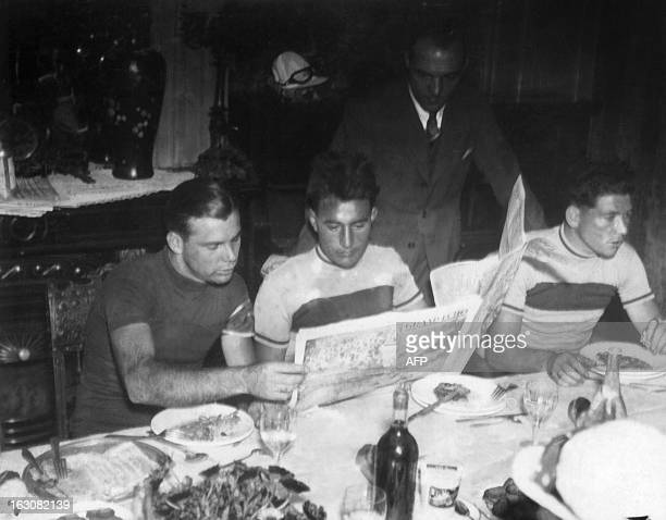 Swiss racing cyclist Paul Egli reads the newsppaper during dinner after the 2nd stage MetzBelfort of the Tour de France on July 10 1934