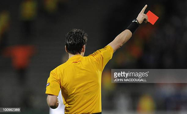 Swiss referee Massimo Busacca shows Olympique Lyonnais' Brazilian defender Cris a red card during the second leg UEFA Champions League semifinal...