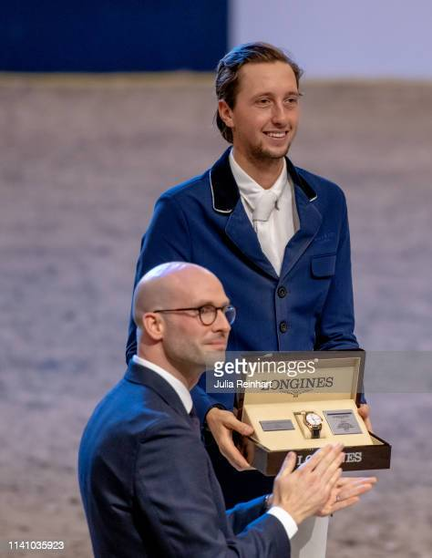 Swiss rider Martin Fuchs receives his runners up prize of Longines' Mathieu Baumgartner during the price giving ceremony for the 2019 Longines FEI...