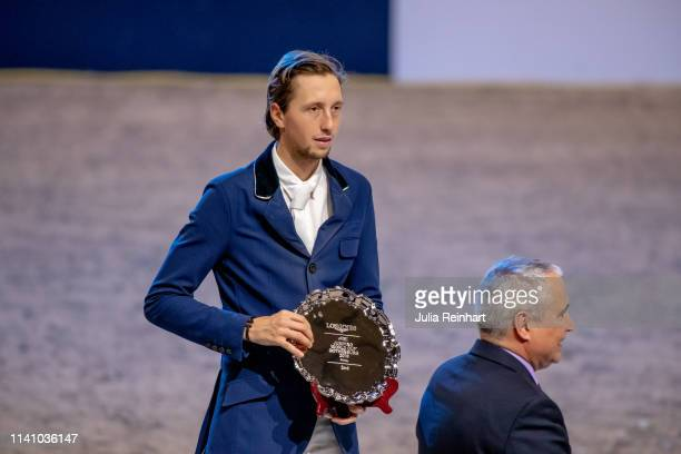 Swiss rider Martin Fuchs receives his runners up trophy of FEI President Ingmar De Voss during the price giving ceremony for the 2019 Longines FEI...