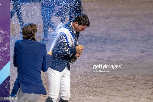 Swiss rider Martin Fuchs sprays Steve Guerdat with champagne during the price giving ceremony for the 2019 Longines FEI Jumping World Cup Final...