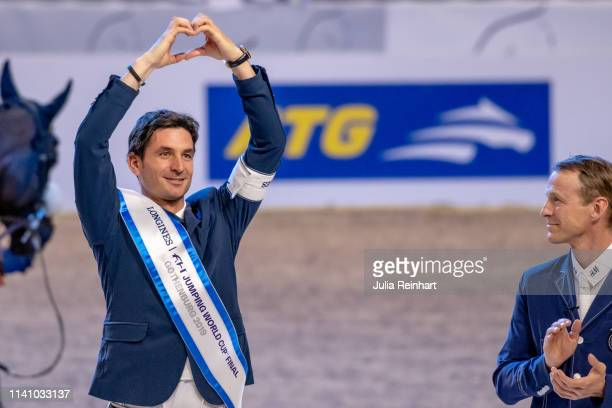 Swiss rider Steve Guerdat celebrates his victory as third place Peder Fredricson from Sweden applauds during the price giving ceremony for the 2019...