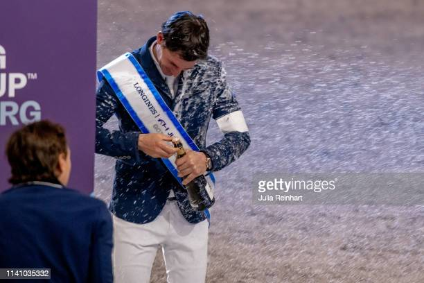 Swiss rider Steve Guerdat gets sprayed with champagne during the price giving ceremony for the 2019 Longines FEI Jumping World Cup Final during the...