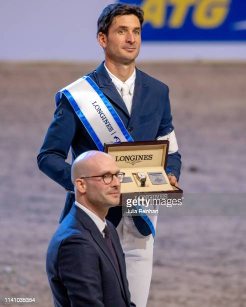 Swiss rider Steve Guerdat receives his winners prize of Longines' Mathieu Baumgartner during the price giving ceremony for the 2019 Longines FEI...