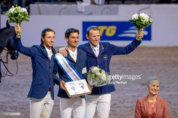 Swiss riders Martin Fuchs and Steve Guerdat and Peder Fredricson from Sweden celebrate during the price giving ceremony for the 2019 Longines FEI...
