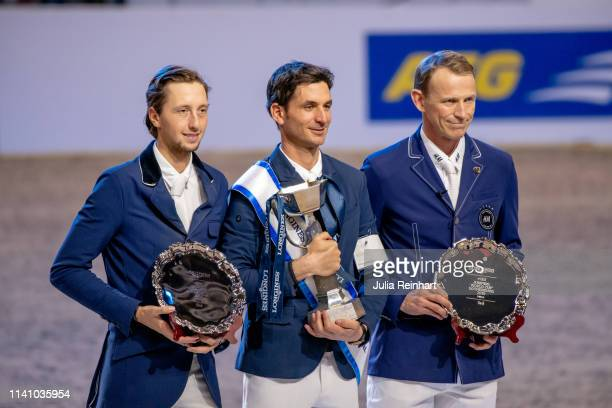 Swiss riders Martin Fuchs and Steve Guerdat and Peder Fredricson from Sweden show off their trophies during the price giving ceremony for the 2019...