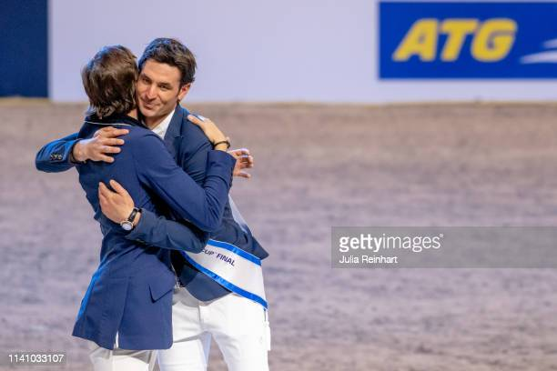 Swiss riders Martin Fuchs and Steve Guerdat embrace during the price giving ceremony for the 2019 Longines FEI Jumping World Cup Final during the...