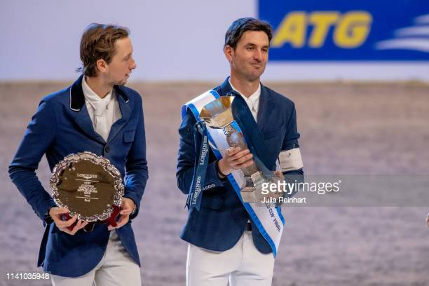 Swiss riders Martin Fuchs and Steve Guerdat show off their trophies during the price giving ceremony for the 2019 Longines FEI Jumping World Cup...