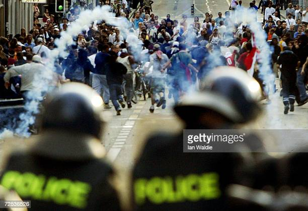 Swiss riot police in foreground fire tear gas at anti-G8 protesters June 1, 2003 in Geneva, Switzerland. After thousands of protesters rallied...