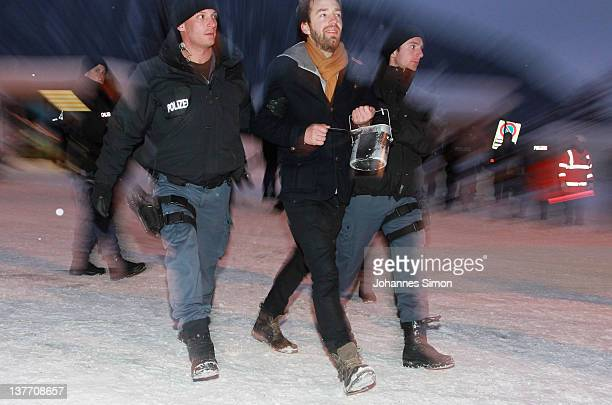 Swiss riot police men arrest an Occupy protester checking personal datas in front of the main gate to Davos congress center on January 25 2012 in...
