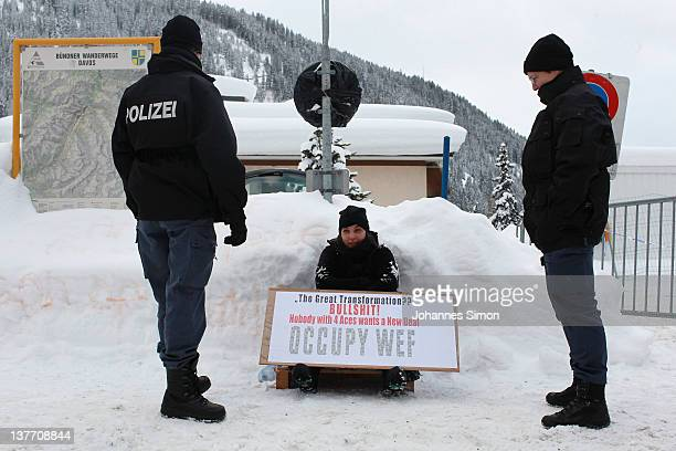 Swiss riot police men frame an Occupy protester checking personal datas in front of the main gate to Davos congress center on January 25 2012 in...