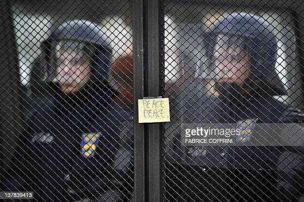 Swiss riot police stand behind fences adorned with a postit during a demonstration by members of 'Occupy WEF' on January 28 against the World...