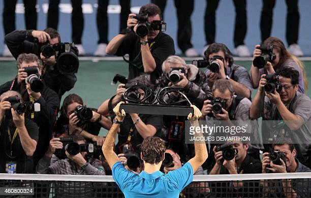 Swiss Roger Federer celebrates with his trophy in front of photographers after winning against French JoWilfried Tsonga their Paris Tennis Masters...