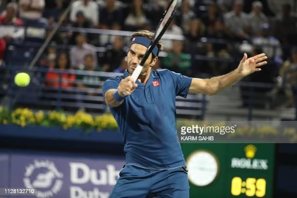 Swiss Roger Federer returns the ball to Hungarian Marton Fucsovics during their quarter final match at the ATP Dubai Duty Free Tennis Championship in...