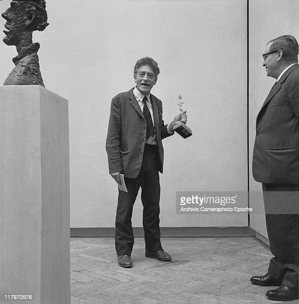 Swiss sculptor Alberto Giacometti wearing a blazer and a tie standing in the exhibition room next to the sculpture 'La Grande Tete De Diego' holding...