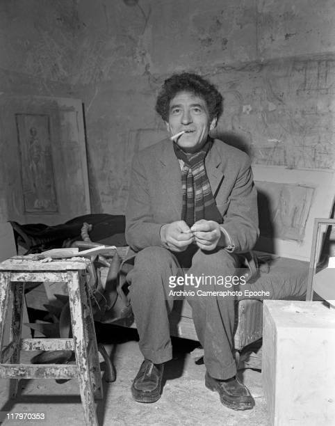 Swiss sculptor Alberto Giacometti wearing a suit and a striped scarf portrayed while sitting on an armchair in his studio surrounded by frames and...