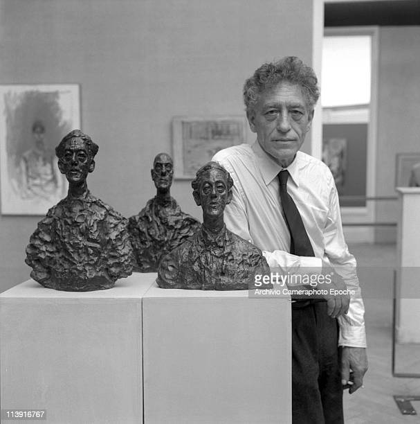 Swiss sculptor Alberto Giacometti wearing a white shirt and a dark tie presents three of his bust sculptures at 31st Art Biennale Exposition in...
