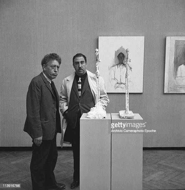 Swiss sculptor Alberto Giametti with the painter Giuseppe Santomaso next to Giacometti's sculptures at 31st Art Biennale in Venice 1962