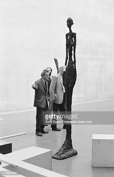 Swiss sculptor and painter Alberto Giacometti at the Tate Gallery with one of his sculptures London July 1965 With him are David Sylvester and Robin...
