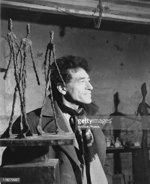 Swiss sculptor and painter Alberto Giacometti in his Paris studio circa 1949 On the left is one of his 'Three Men Walking' sculptures