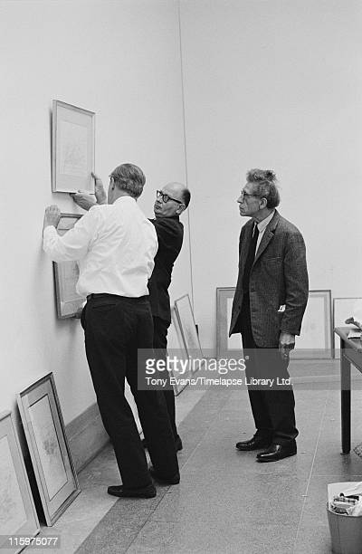 Swiss sculptor and painter Alberto Giacometti looks on as his friend Louis Clayeux and Robin Campbell hang a piece of work at the Tate Gallery London...