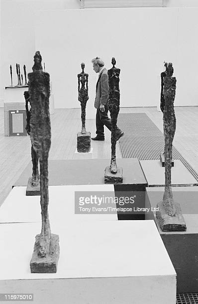 Swiss sculptor and painter Alberto Giacometti with some of his sculptures at the Tate Gallery London July 1965