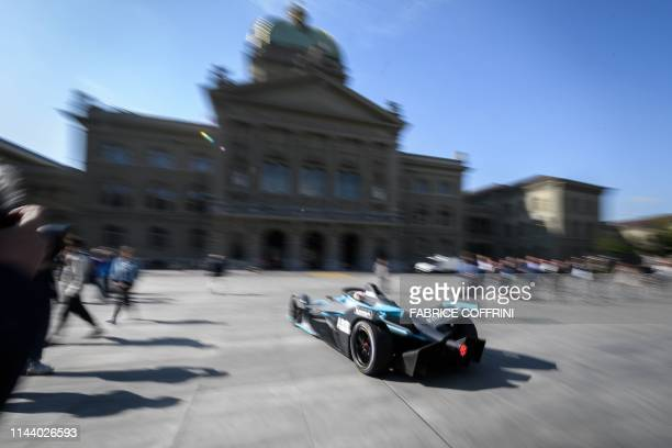 Swiss Sebastien Buemi drives his car in front of the Swiss House of Parliament during a promotion event of the Swiss stage of the Formula E electric...