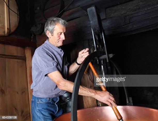 スイスの羊農家スモーキー スイス マウンテン シャレーでの伝統的な方法でチーズになります - 大釜 ストックフォトと画像