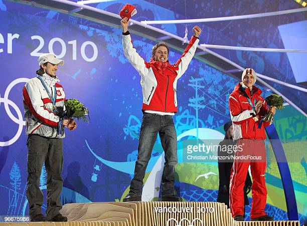 Swiss Simon Ammann celebrates on the podium as Poland's Adam Malysz and Austrian Gregor Schlierenzauer look on during the medal ceremony for the Ski...