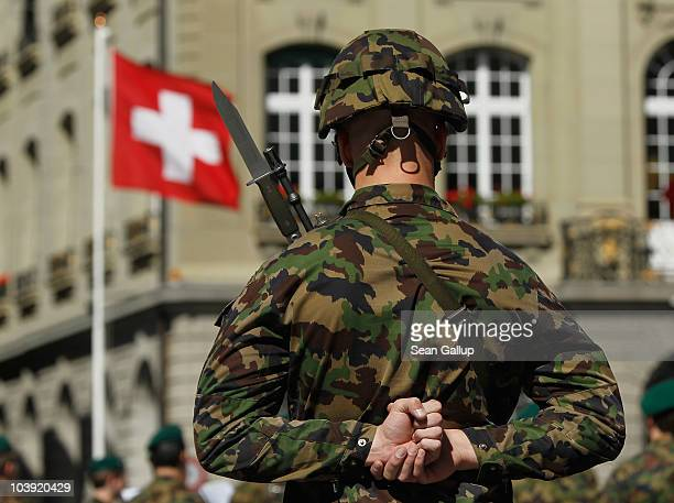Swiss soldier stands at attention in front of a Swiss flag before the arrival of German President Christian Wulff on September 8 2010 in Bern...