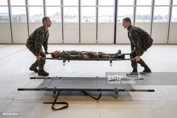 Swiss soldiers exercices with stretcher at the Swiss Air Force Base of Payerne on March 28 2018 In neutral Switzerland military service is obligatory...