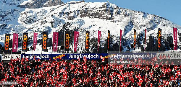 Swiss supporters wave Swiss flags as they watch the podium ceremony of the men's downhill of the FIS Ski World cup in Wengen on January 17 2009 Swiss...