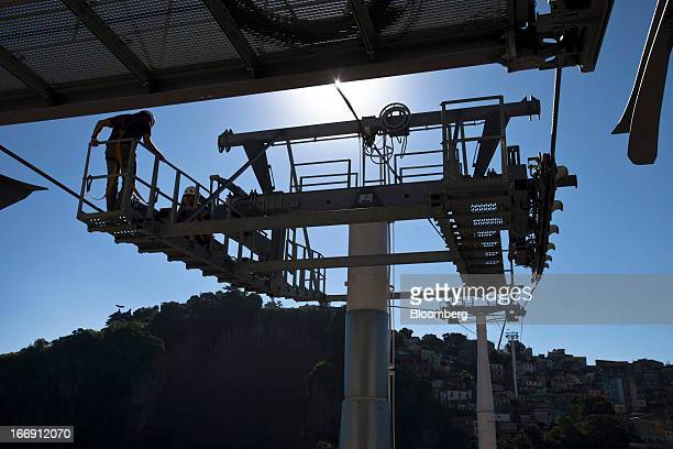 Swiss technicians wait for the electricity to return in order to test cable cars at a station in Rio de Janeiro, Brazil, on Tuesday, April 16, 2013....
