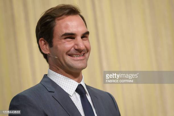 Swiss tennis champion Roger Federer laughs during the unveiling of a nine-meter high chocolate fountain at the new 'Lindt Home of chocolate' of the...