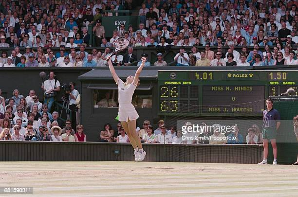 Swiss tennis player Martina Hingis leaps and throws her arms in the air in celebration after beating Czech tennis player Jana Novotna 26 63 63 in the...