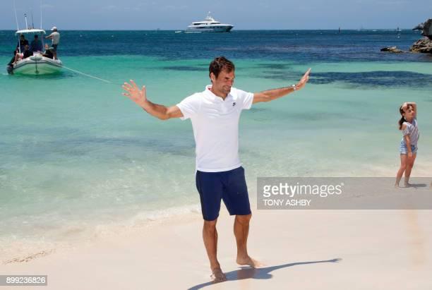 Swiss tennis player Roger Federer gestures as he walks along a beach at Rottnest Island off the coast of Western Australia on December 28 2017 / AFP...