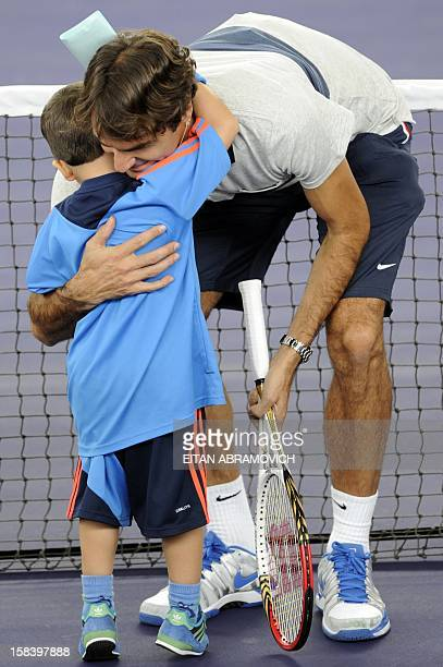 Swiss tennis player Roger Federer hugs a boy during a clinic in Bogota Colombia on December 15 2012 AFP PHOTO/Eitan Abramovich