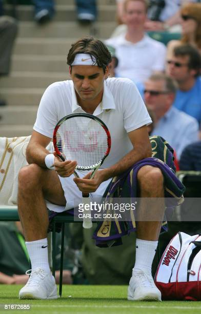 Swiss tennis player Roger Federer looks at his racket as he plays against Slovakia's Dominik Hrbaty during their first round match of the 2008...