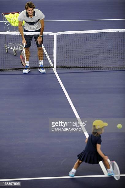 Swiss tennis player Roger Federer plays with a girl during a clinic in Bogota Colombia on December 15 2012 AFP PHOTO/Eitan Abramovich