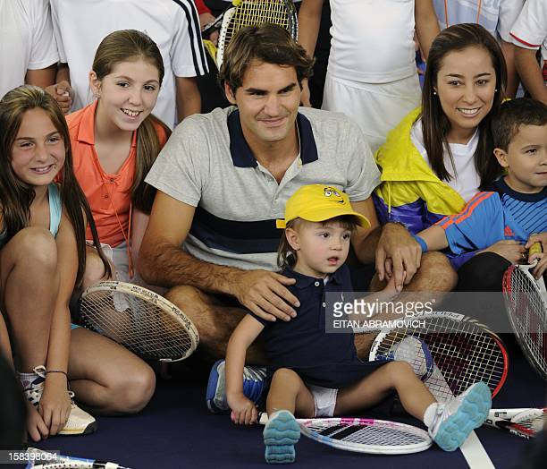 Swiss tennis player Roger Federer pose with supporters during a clinic in Bogota Colombia on December 15 2012 AFP PHOTO/Eitan Abramovich