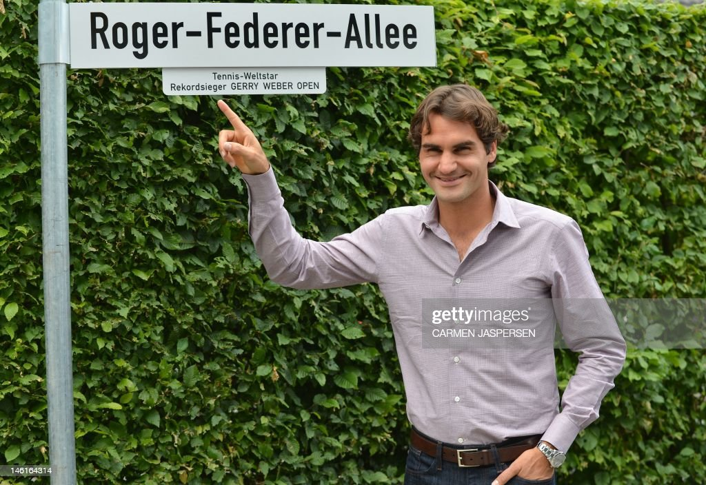 Swiss tennis player Roger Federer poses by a street sign reading his name near the Gerry Weber Stadium in the city of Halle western Germany on June 11, 2012 where the Halle ATP open started today. Federer has won the tournament five times.