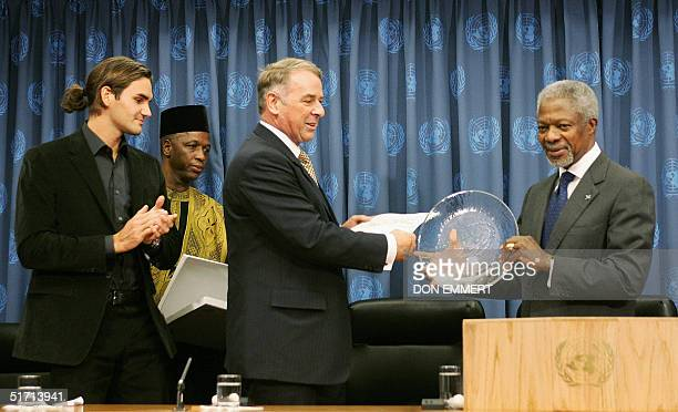 Swiss tennis star Roger Federer applauds as and United Nations Special Advisor on Sport and Development Adolf Ogi presents a plaque to UN...