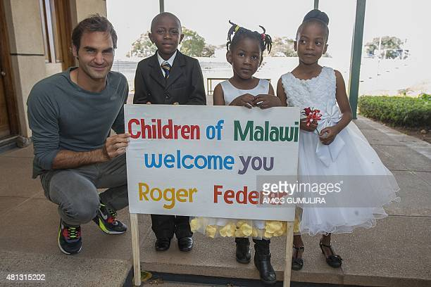 Swiss tennis star Roger Federer poses with Malawian children at Kamuzu International Airport on his arrival for a visit to Malawi July 19 2015 Roger...