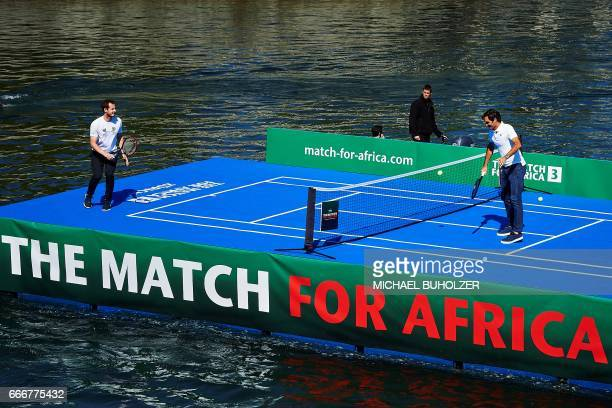 Swiss tennis superstar Roger Federer returns a ball to world number one Britain's Andy Murray during a promotion on a raft on the river Limmat before...