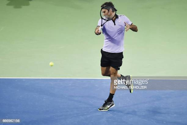 Swiss tennis superstar Roger Federer returns the ball to world number one Britain's Andy Murray during a charity match The Match for Africa 3 on...
