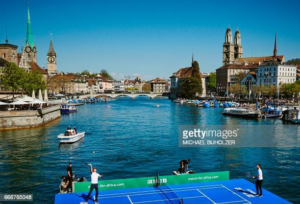 Swiss tennis superstar Roger Federer serves a ball to world number one Britain's Andy Murray during a promotion on a raft on the river Limmat before...
