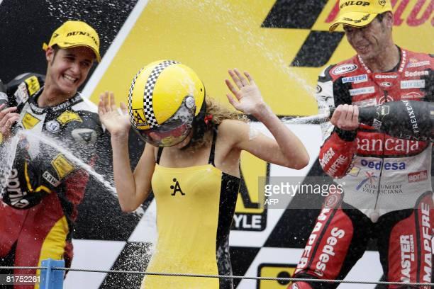 Swiss Thomas Luthi and Spanish Alvaro Bautista spray a hostess at the Dutch Grand Prix 250cc podium on June 28 2008 Bautista riding an Aprilia won...