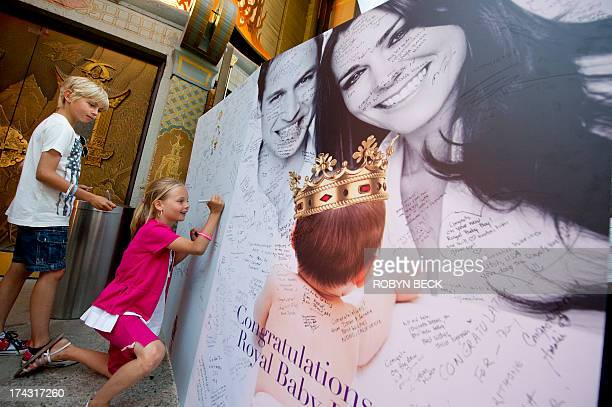Swiss tourists Andrea and his sister Sara sign a giant card congratulating Britain's Prince William and Kate Duchess of Cambridge on the birth of...